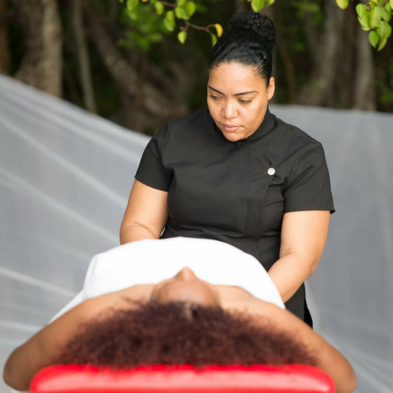 Shivonne of Soothing Touch Massage standing over a female client outdoors at Marion Bay, Buccoo, Tobago about to begin a sunset massage